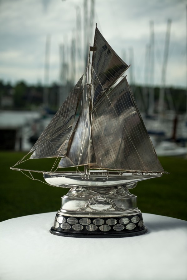 This is a large, silver plated model of a gaff-rigged sailboat